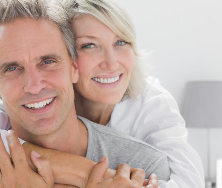 Affectionate,Couple,Smiling,At,Camera,At,Home,In,Bedroom